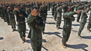 Syrian Internal Security Forces are sworn in during their graduation ceremony, at Ain Issa desert base, in Raqqa province, northeast Syria, Thursday, July 20, 2017. Some 250 residents of Syria's Raqqa province are the latest batch to graduate from a brief U.S-training course that is preparing an internal security force to hold and secure areas as they are captured from Islamic State militants. (AP Photo/Hussein Malla)